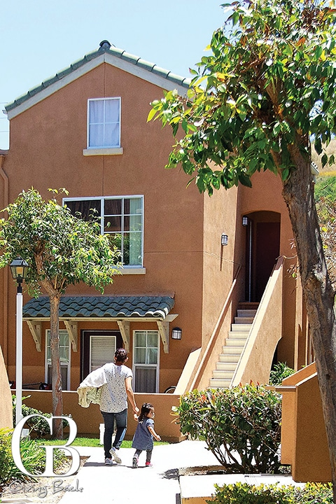 A resident walks with her daughter at the Laurel Tree Apartments in Carlsbad