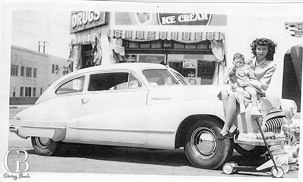 Cousins Tom Cresci and Florence DeLuca sit atop a classic automobile in