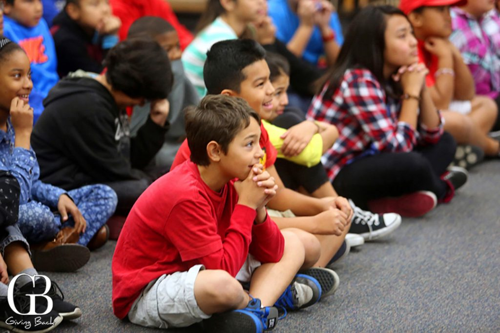 Elementary school students watching a performance of the  POP Tour